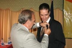 El Dr. Orlando Crespo Vargas mientras condecora al Dr. Fauzi Bachá por su dedicación y méritos en favor de la educación médica continua.