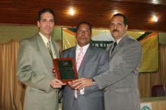 El Dr. Bachá Arbaje y el Lic. Arnol Ramsés mientras entregaban placa de reconocimiento al Dr. Luis Pichardo por su ardua labor en favor de la educación de los graduados.