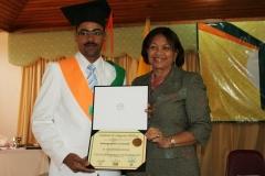 Dr. Tomás Ventura Martínez recibiendo su diploma de las manos de la Lic. María Elena Cruz.