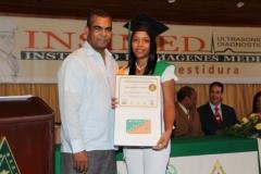 El Dr. Luis Felipe Encarnación, del Colegio Médico Dominicano, hace entrega del certificado de Sonografista General a la Dra. Aracelis Santana González.