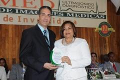 Dr. Bachá Arbaje entrega reconocimiento a la Lic. María Elena Cruz, Honorable y Magnífica Rectora de UTESA, por depositar su confianza en la familia INSIMED